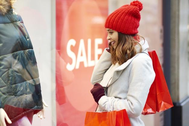 garota-animada-olhando-para-a-vitrine-durante-as-compras-de-inverno- via gpoitstudio freepik